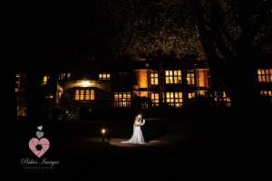 Bride and groom posed at night in front of venue. Pickin Images Photography