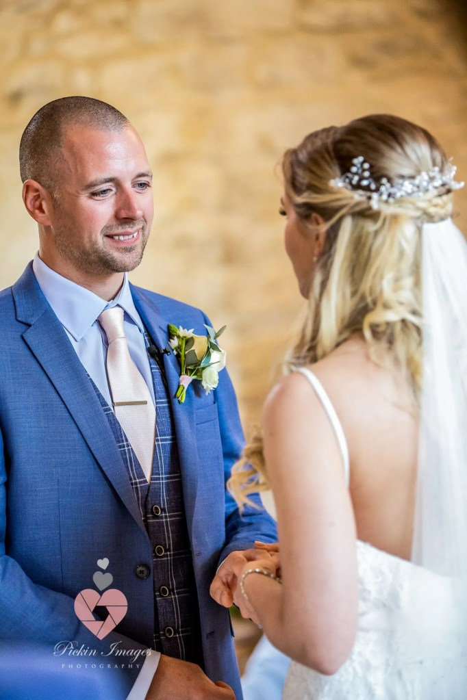 Groom saying his idos at the alter in Kingscote barn. Pickin Images Photography
