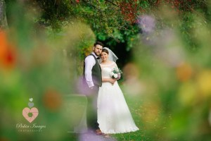 Bride and groom posed and shot through bushes by photographer pickin images for photos.