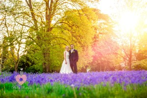 Bluebell wild flowers in a early summer meadow with the bride and groom. Caught by photographer pickin images for photos.