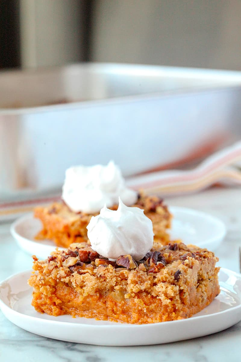 Two slices of pumpkin dump cake, one in front of the other, both with whipped topping on top