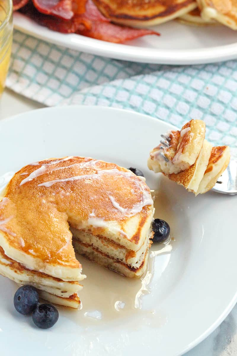 plate of pancakes with a fork on plate that has a bite of pancakes