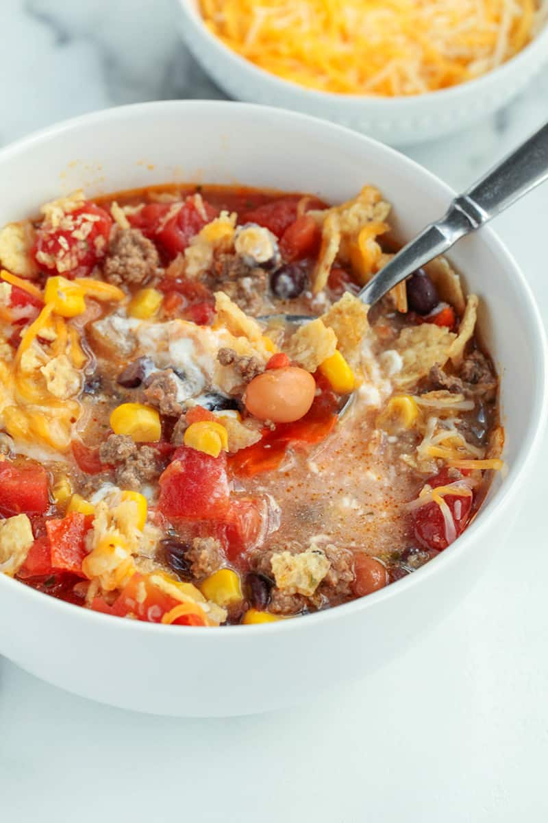 Taco soup with sour cream and shredded cheese all stirred into the hot soup