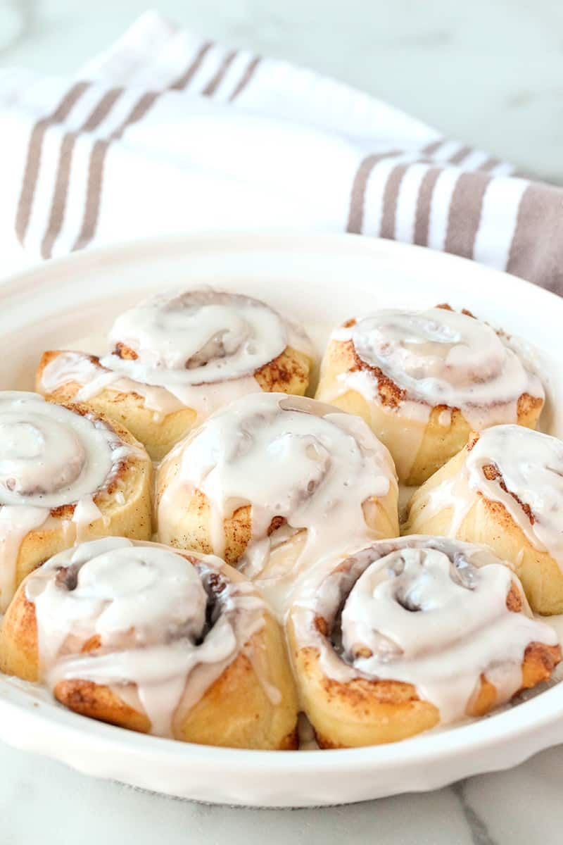 frozen bread dough made into easy cinnamon rolls with frosting in a pie plate