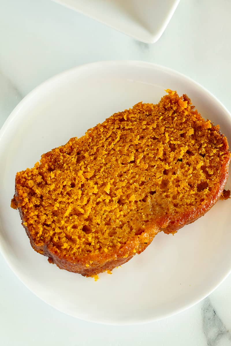 A single slice of pumpkin bread on a white plate