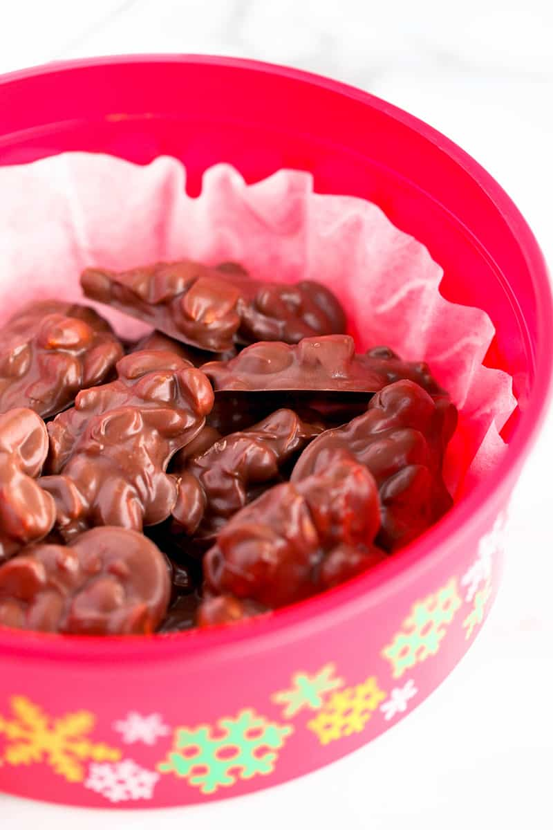 A plastic red bowl with colorful snowflakes on the sides and filled with crockpot candy