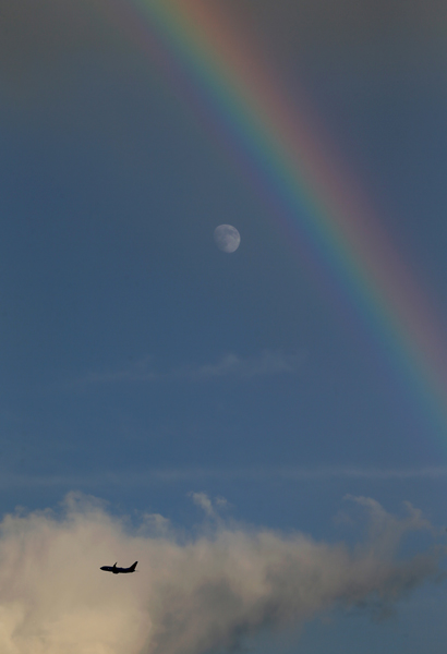 A rainbow forms close to the near-full moon on August 7, as a jetliner leaves Boston's Logan airport.