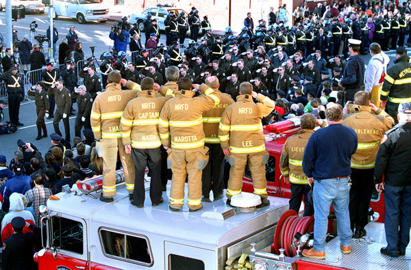 As the procession passes by the home Fire Station of 2 of the dead Worcester Firefighters, mutual aid firefighters (from No. Reading and Marblehead) salute back from on top of Marblehead Fire Engine. Staff Photo: Mark Garfinkel
