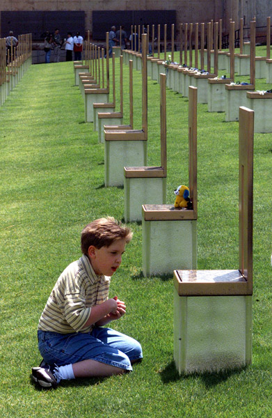 "Brandon Denny, age 9 years, also known a ""Miracle Boy"" due to his improbable survival living against all odds after having a hole the size of a fist punched thru his brain in the Murrah Federal Bldg bombing, prays at a chair that symbolizes his dead friend Chase Smith who was in the same day care in the bldg but did not survive."