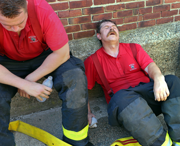08/07/2015-Boston,MA. Boston firefighters from left Kevin Ranahan and Jeremy Nelson, of Ladder company 4 take a break from fighting a 3 alarm fire at 6 Waverly St. in Roxbury today. Staff photo by Mark Garfinkel