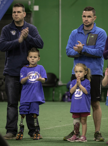 Braylon O'Neill, age 6 years, and his dad Mike, both at left, and Gracie Fennelly, age 4 years, and her dad Kerian are seen at the 3rd Ossur Boston Running and Mobility Clinic, Saturday morning.