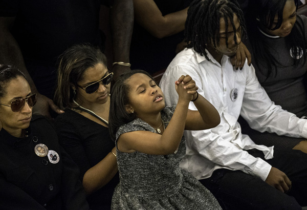 11/06/2015-Boston,MA. Saniyah Brathwaite, the granddaughter of murder victim Clive Francis Sr., prays during a solemn moment at her grandfather's funeral at Greater Love Tabernacle Church, Friday morning. She is sitting on the lap of her mother Keosha Francis, Clive's daughter.