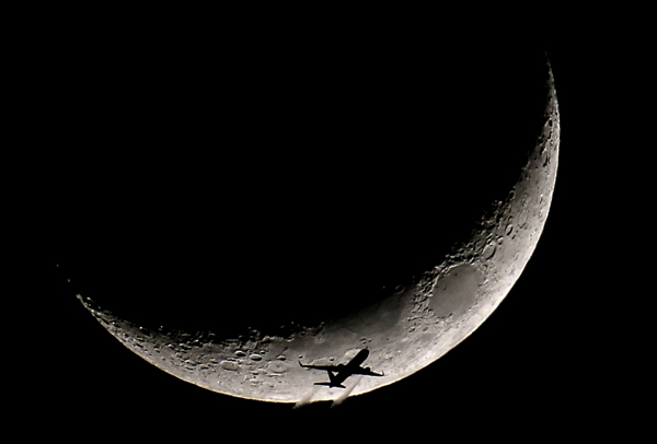 01/23/2015-Boston,MA. A high altitude passenger jet crossing in front of tonight's crescent moon.