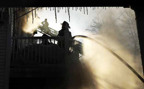02/06/2015-Revere,MA. Firefighters battle flames, smoke and cold air at the scene of a 3 alarm fire on Reservoir Rd. Friday morning.