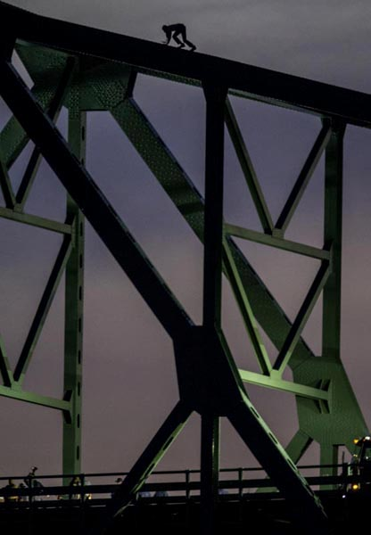 06/10/15-Boston,MA. A man, threatening to jump from Boston's Tobin Bridge, is seen climbing the bridge this evening as a police negotiator, bottom left, speaks to him through a bull horn. The man climbed down after 2 hours atop the bridge.