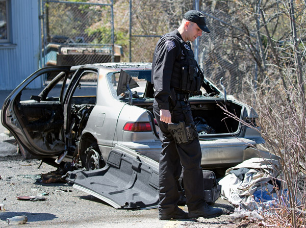 04/27/2016-West Roxbury,MA. A police officer is seen near the remains of a car that was involved in a long-duration police pursuit that began in Walpole, and ended in West Roxbury. The car caught fire at the 1400 block of VFW Parkway. Staff Photo by Mark Garfinkel