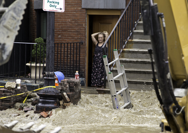 October 21, 2016-Boston,MA. A stunned Mirtha Colon, a resident of 10 Dartmouth St. apt B, watches firefighters scurry into position in the first moments after a trench collapse and water leak killed two workers Friday afternoon on Boston's Dartmouth street. CREDIT Boston Herald staff photo by Mark Garfinkel. NO BOSTON (Boston OUT) No sales No Mags