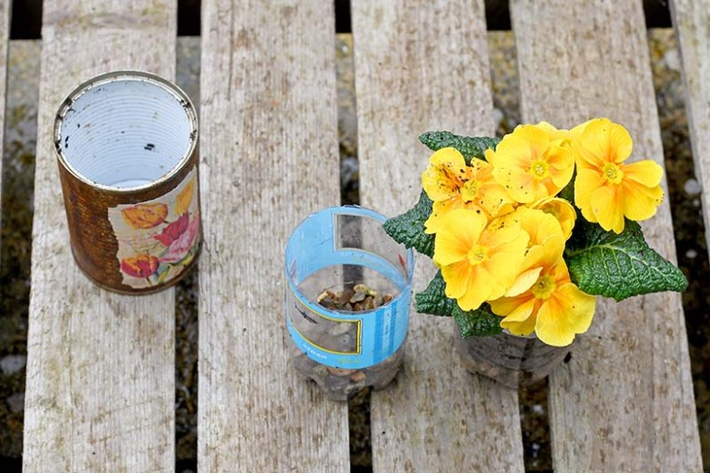 Planting flowers in decoupaged tin cans