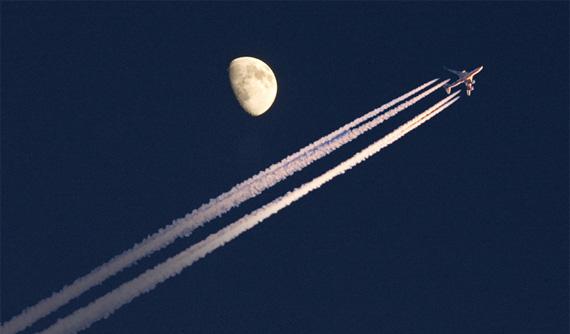 plane flying past moon
