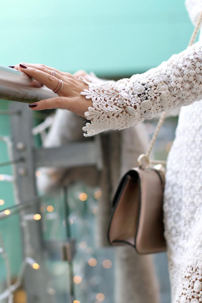 Weihnachtslook mit weißem Spitzenkleid, hellgrauem Wollmantel und rosa metallic Glam Lock Tasche von Valentino
