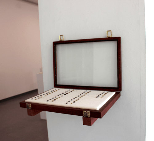 "Lana Abu-Shamat - ""35 Original 35 Replicates,"" 2014, Coffee beans from Nablus, Palestine, self-hardening clay, English and Arabic numeral labeling, collectibles display case, linen, 18 x 12 x 2 inches."