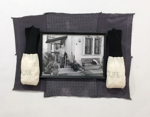 """Sermin Kardestuncer - """"Live Life (dedicated to Baba),"""" 2008–2019, Socks, cotton filling, thread, a framed B & W photograph on fabric, 18 X 24 X 2 inches  """"I wrote an homage to my father and his summer home in Ayvalik, Turkey after he died in 2015. The B & W photo used in this work, 'Live Life,' is taken in front of this home. 'Hayati yasa,' ('Live life' in Turkish) he said, when I rushed to visit him at his bedside a few months before he died and when he was loosing all cognitive abilities. Since then, I search for the hidden meaning or a message to 'Live Life.' By stitching the words on soft fabric that hangs from each side of the photograph like gentle gloves, I try to gain courage to live up to his wishes."""""""