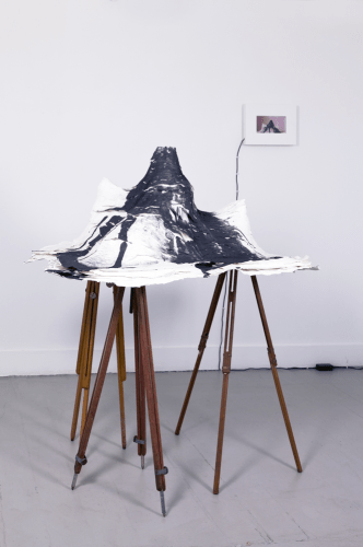 """A Once & Future,"" 2013, 3 tripods, cardboard, papier-mâché, vinegar, baking soda, graphite, video loopA Once & Future,"" A Once & Future, 2013, 3 tripods, cardboard, papier-mâché, vinegar, baking soda, graphite, video loop, Approximately 5 x 3 x 5 feet"