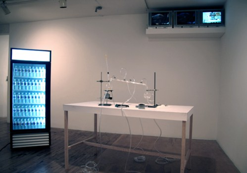 Homeostatic Feedback Loop #1 (Natural Body Water) - 2003-06, Table with glass distillation kit, three video monitors, DVD, refrigerator with purified body water, glass vials with distilled salt, and sketches