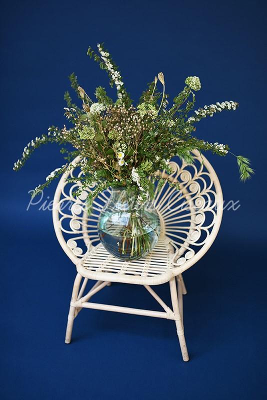 Bouquet de fleurs dans un vase sphérique en verre posé sur un chaise pour les pros