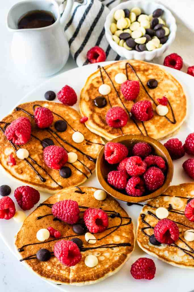 Sourdough Pancakes topped with chocolate drizzle and raspberries