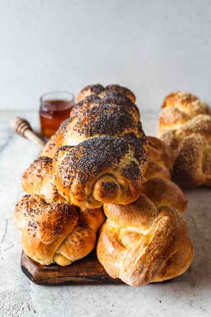 3 stacked loaves of challah bread, and one loaf in the back, also a container of honey in the background.