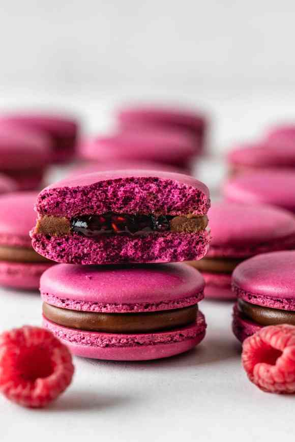 pink macarons filled with raspberry jam and chocolate ganache sliced in half showing the inside of the macarons.