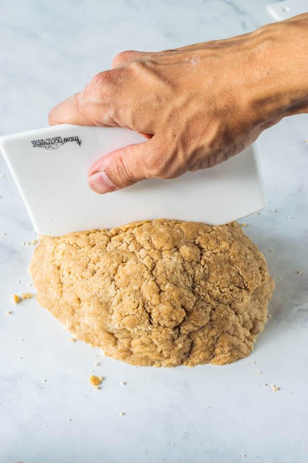 cutting dough in half with a bowl scraper