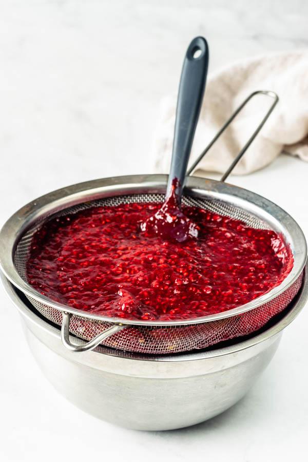 straining raspberry jam seeds