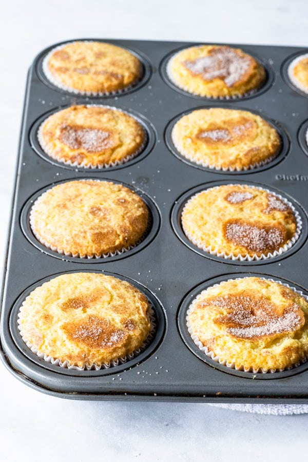 cupcakes in cupcake tin baked with cinnamon sugar topping