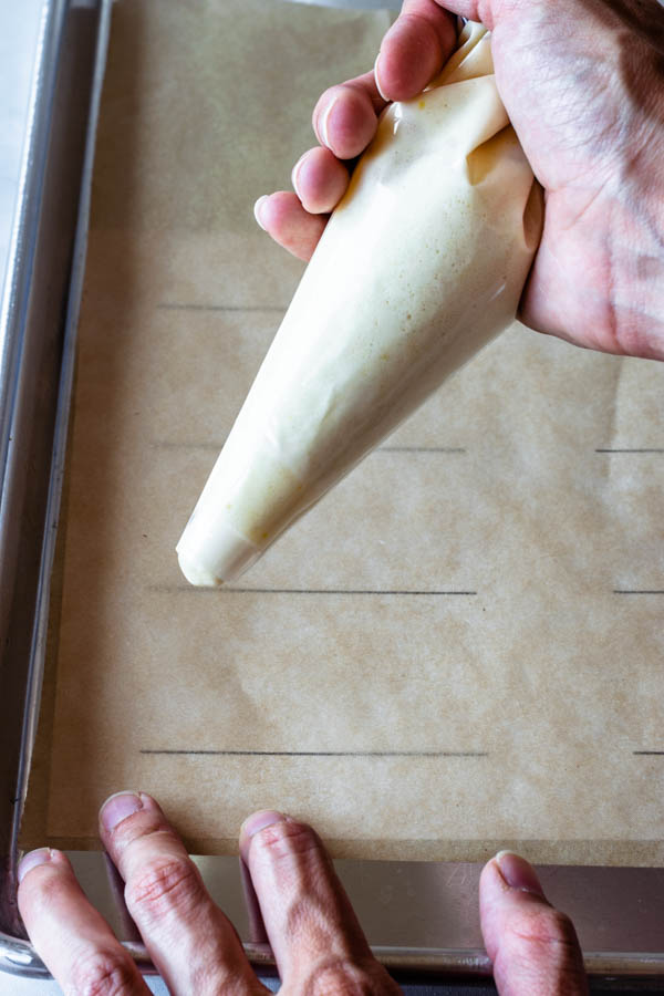 piping ladyfinger cookies in a pan lined with parchment paper and a template under