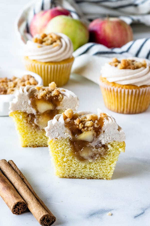 Apple Crisp Cupcakes with cinnamon cream cheese frosting, filled with apple pie filling cut in half