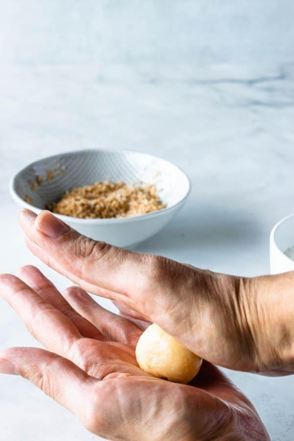 rolling coconut fudge into balls between buttered hands