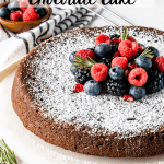 flourless Olive Oil Chocolate Cake dusted with powdered sugar and topped with fresh berries