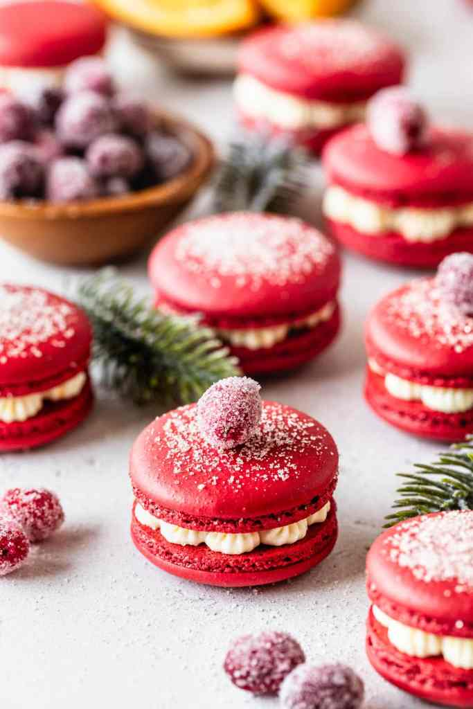 cranberry macarons topped with sugar and with sugared cranberries, filled with orange buttercream.