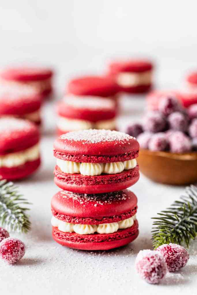 2 red macarons stacked, filled with cranberry sauce and orange buttercream.
