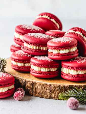cranberry macarons with dusting of sugar on top, on top of a wooden board.