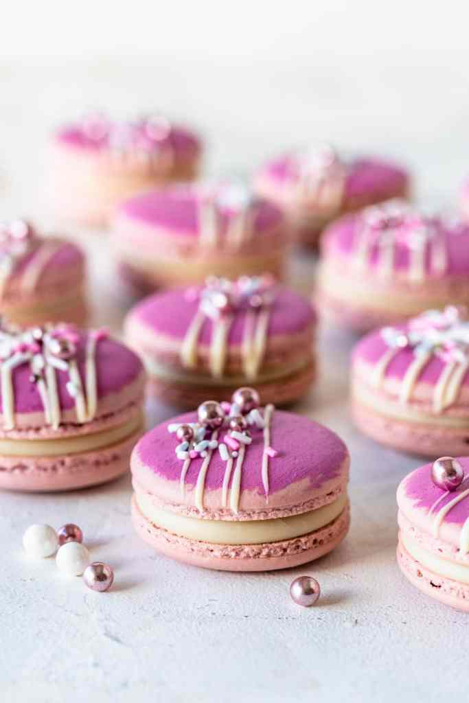 pink macarons topped with a drizzle of white chocolate and sprinkles.