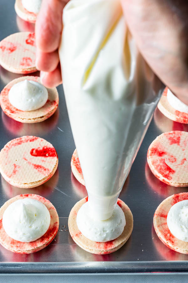 piping peppermint buttercream on top of macarons