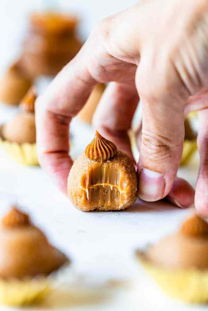 hand holding a dulce de leche truffle with a bite taken out of it.