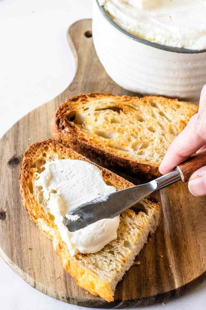 spreading homemade ricotta on toast