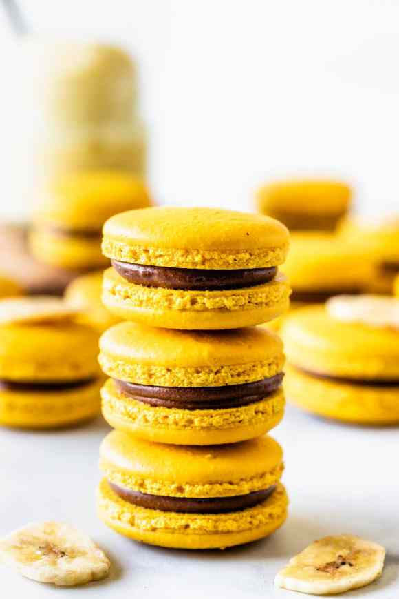 stacked yellow macarons with chocolate filling and a dried banana chip on top