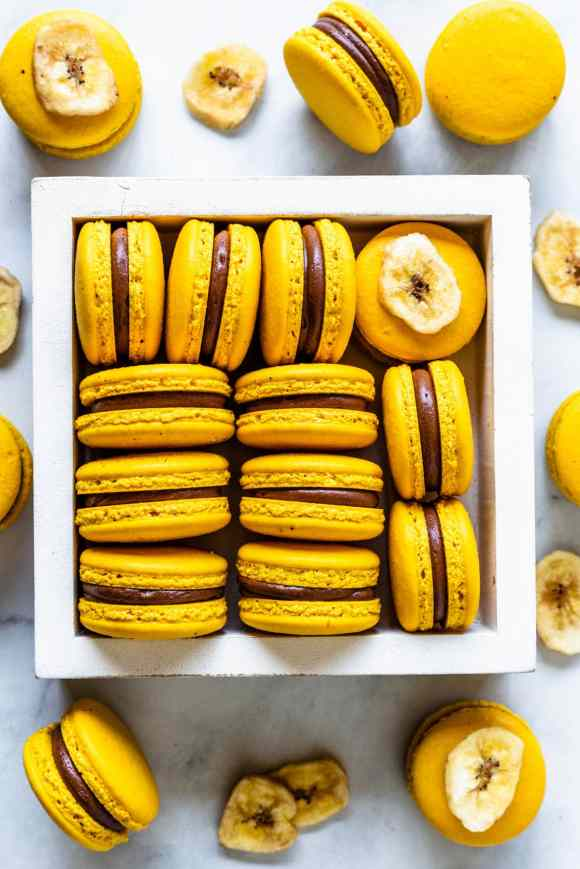 Banana Macarons yellow macarons in a box with chocolate and banana pudding filling, bird's eye view