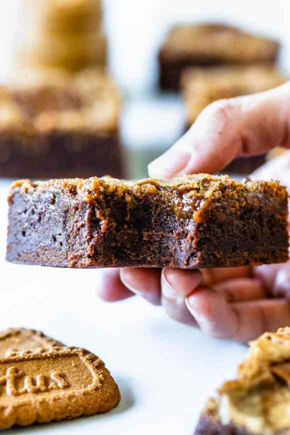 hand holding a slice of bitten biscoff brownie
