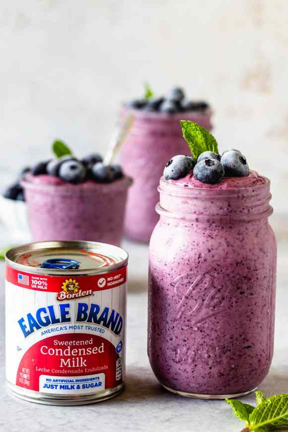can of condensed milk and blueberry slushie in a mason jar topped with mint leaf and frozen blueberries and a spoon